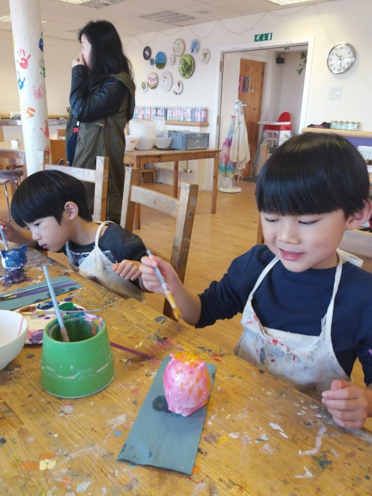 two boys at a table painting ceramic pots