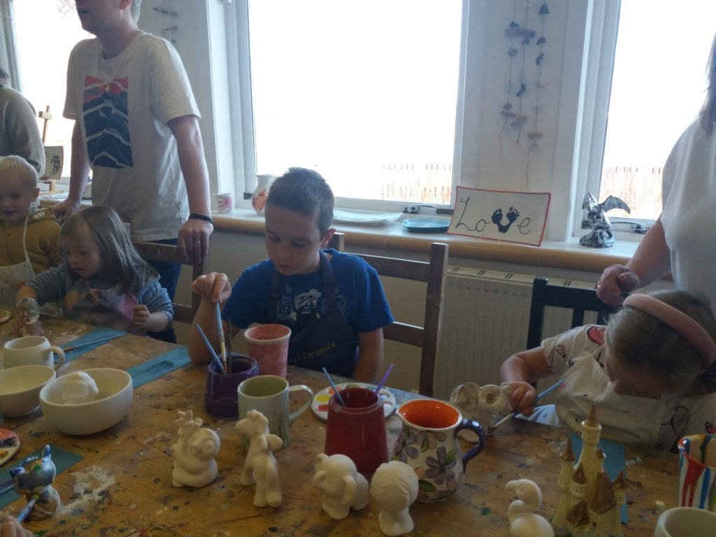 a boy painting at a table with lots of ceramic ornaments
