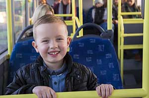 boy sitting on a bus, smiling