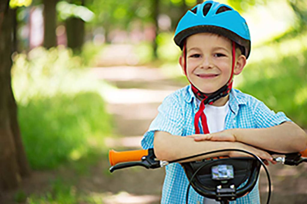 Boy wearing a helmet, with arms crossed, sitting on a bike